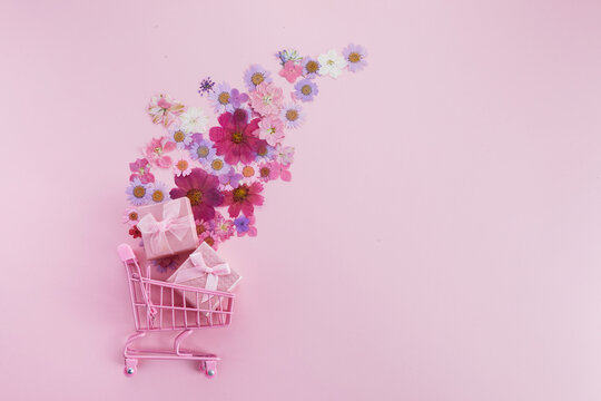 Flowers fly out of the pink shopping cart on a pink background. Season sale, spring shoping concept. Valentines day.