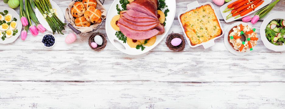 Traditional Easter ham dinner. Overhead view top border on a white wood banner background with copy space. Ham, scalloped potatoes, vegetables, eggs, hot cross buns and carrot cake.