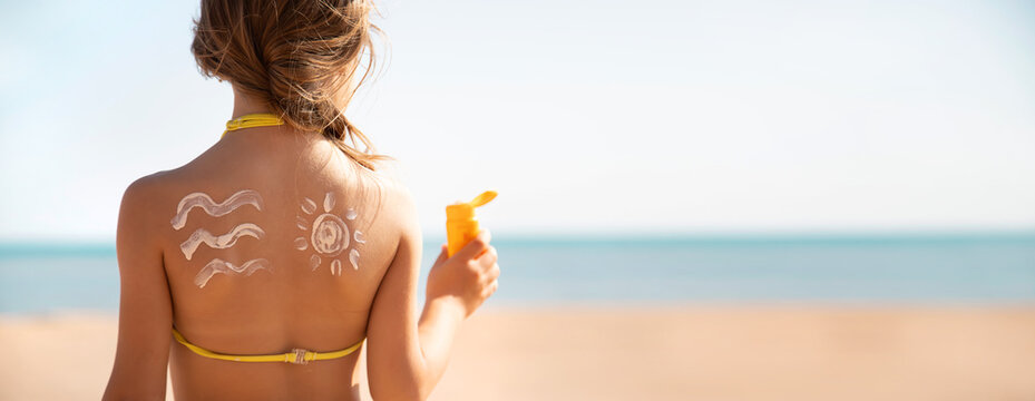 Child girl smears sun cream on her face. Selective focus.
