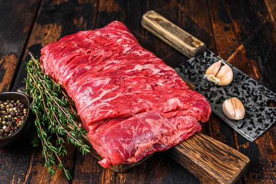 Big piece of raw beef brisket cut meat with herbs and butcher cleaver. Dark wooden background. Top view