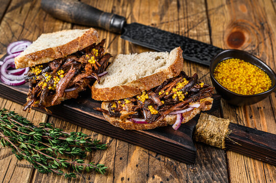 Sandwich with slow smoked pulled pork meat on white bread. wooden background. Top view