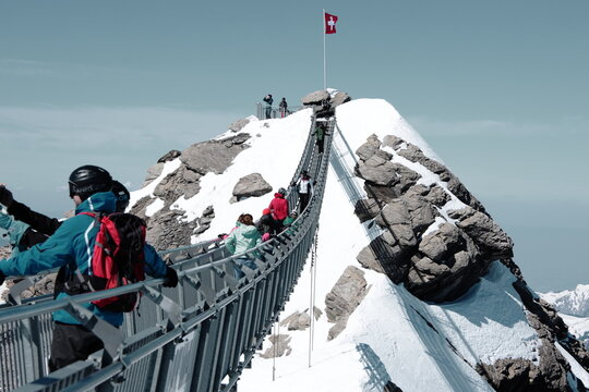Swiss flag on top of Glacier 3000 mountain, tourists on the mountain