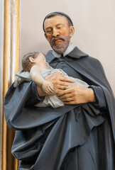 VIENNA, AUSTIRA - OCTOBER 22, 2020: The carved polychome sculpture of St. Vincent de Paul in the church St. John the Evangelst by Josef Urbania (1924).