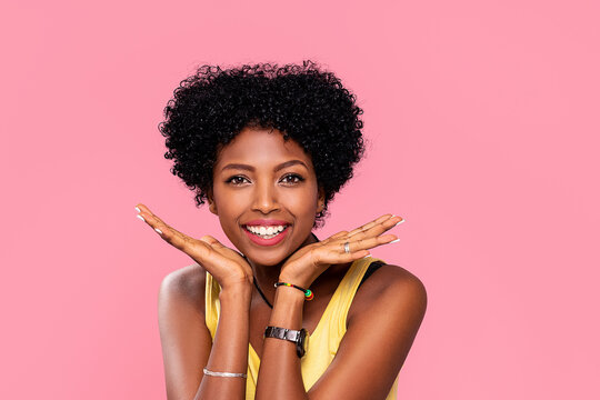Happy young african woman with beautiful smile posing on pink pastel studio background. Attractive afro girl with glamour makeup.