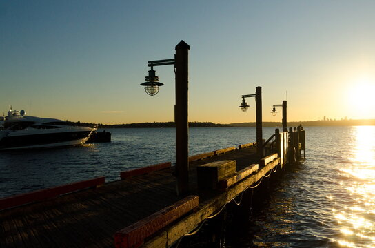 Silhouettes and lamp posts on wooden pier  during  winter sunset