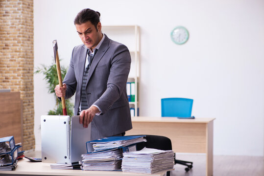 Young employee angry with excessive work holding hatchet