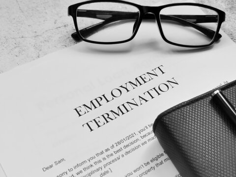 Employment Termination letter with pen,eye glasses and book.