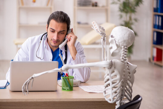 Young male doctor and skeleton patient in the clinic