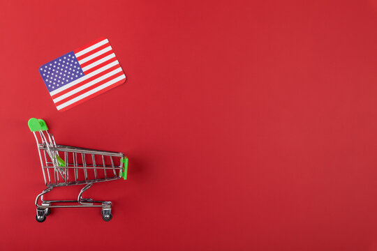 Mini empty supermarket shopping grocery cart, USA flag on red background