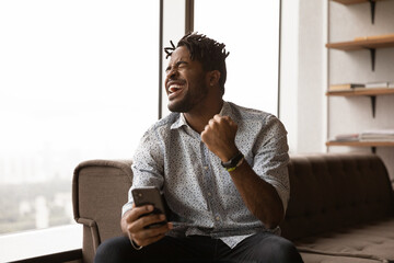 Overjoyed black male hipster blogger receive perfect commercial offer pleasant comment at social...