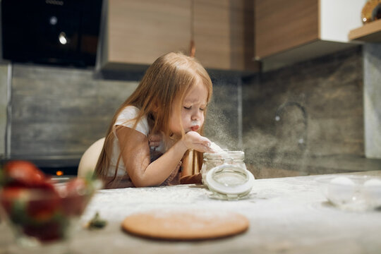 Happy little chef, flour, knead the dough. The cook girl blows on the flour. Home cooking. kitchen