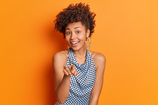 I choose only you. Positive Afro American lady in fashionable clothes points index finger directly at you invites someone for party has stylish hairstyle isolated over vivid orange background.