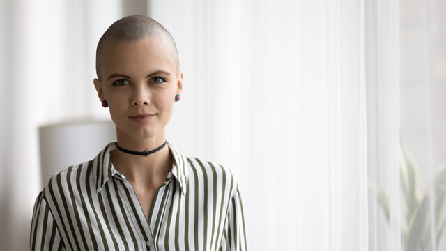 Portrait of smiling millennial Caucasian hairless female designer or artist feel confident at home. Happy young bald shaved hair woman rock lover posing indoors. Subculture, art, hobby concept.
