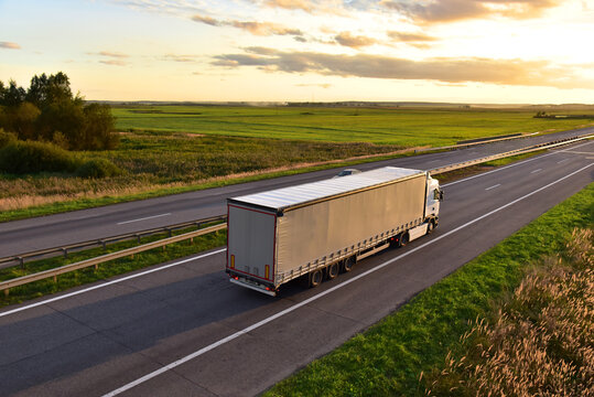 Truck with semi-trailer driving along highway on the sunset background. Goods delivery by roads. Services and Transport logistics. Soft focus. Object in motion.