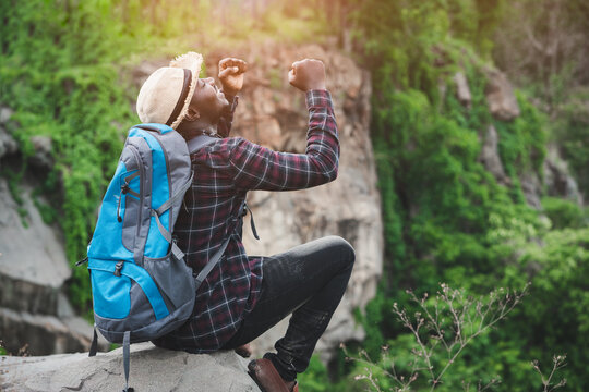 Success african man traveler sitting on the cliff with backpack