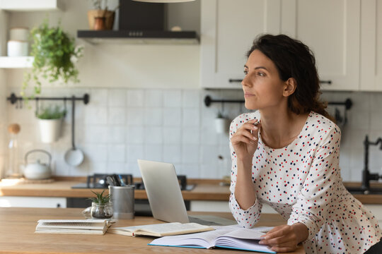 Pensive millennial Caucasian woman distracted from online work look in distance dreaming or thinking. Thoughtful young female study distant on laptop make decision or plan. Education concept.