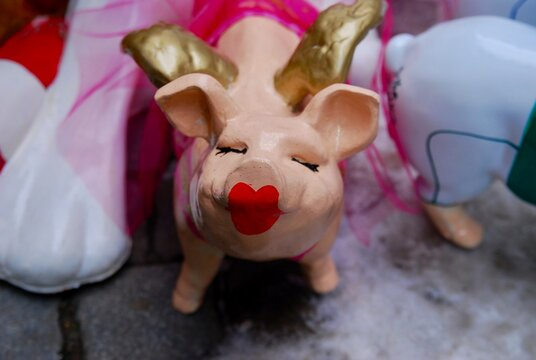 small ceramic toy pig with closed eyes and red lipstick