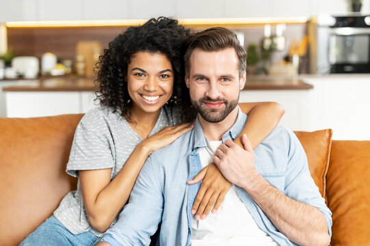 Cheerful multi ethnic couple in love sits on the sofa in embraces and looks at the camera. A tenderly portrait of smiling man and african girl hugging. Love and affection concept