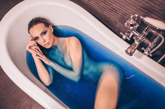 Beautiful young woman with fashion make up, posing bathing in a retro tub full of colored blue cosmic bath bomb water. Spa and beauty salon concept, body and skin care.