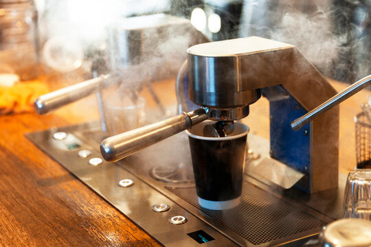 Professional espresso machine pouring takeaway coffee in local cafe.