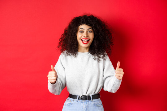 Enthusiastic girl with curly hair and red lips, showing thumbs up and saying yes, agree with you, compliment good work, like something cool, standing on studio background