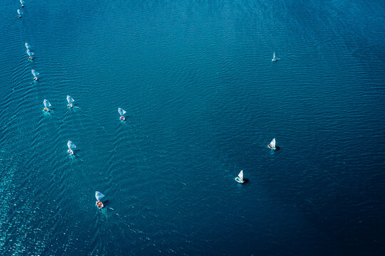 Regatta of small boats on blue lake, aerial view