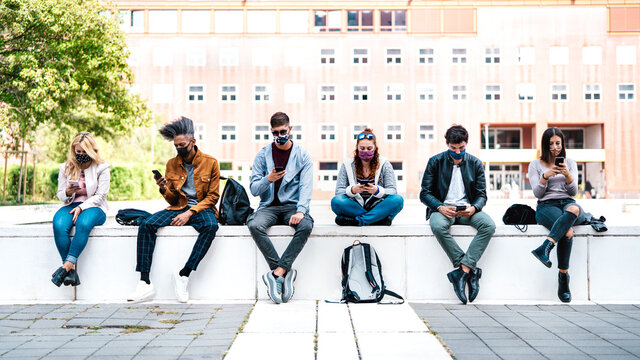 Friends using smart phone covered by mask on Covid third wave - Worried guys and girls watching video news on mobile smartphone - College students sitting at university campus - Focus in central faces