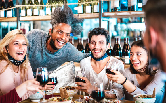 People drinking red wine at fusion bar restaurant - Food lifestyle and new normal concept with happy friends having fun together at fashion diner - Selective focus on face of left afroamerican guy