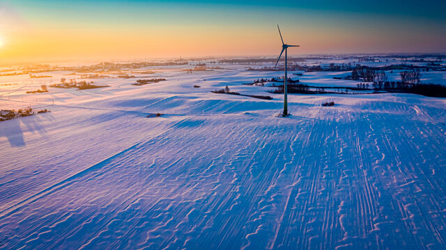 Amazing snowy field and wind turbine at sunrise in winter