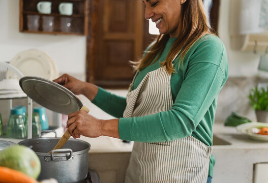Latin mature woman cooking in old vintage kitchen - Smiling mother preparing lunch at home