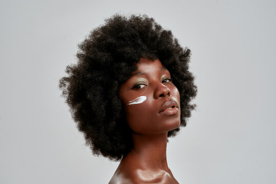 Beauty portrait of young naked african american woman with afro hair looking at camera while posing with cream applied on her face isolated over gray background