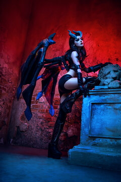 Girl devil in gothic costume and wings and horns
