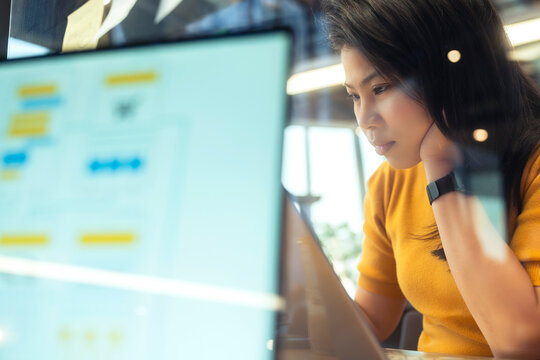 attractive freelance asian female creative person wear casual yellow cloth working with laptop at share area coworking space new lifestyle with thoughful and freshness emotion blur office background
