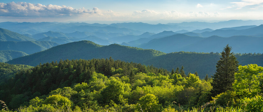A panoramic view of the Smoky Mountains from the Blue Ridge Parkway in North Carolina. Blue sky with  clouds over layers of green hills and  mountains.  Copy space. North Carolina.