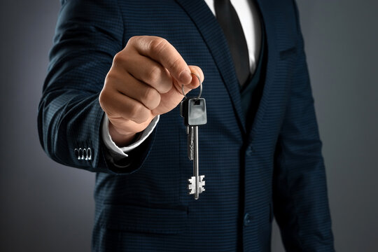 A man in a business suit holds out the keys in his hand. The concept of a realtor, mortgage, your house, home loan. Copy space.