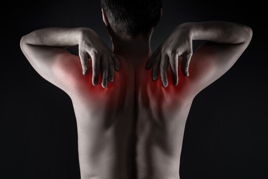 Shoulder blades pain, man with backache on black background
