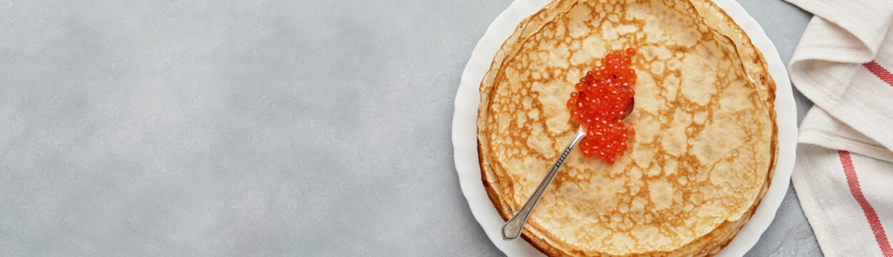 Crepes, thin pancakes, Russian pancakes with red caviar on gray plate. Marble background. Mock up. Copy space. Top view.