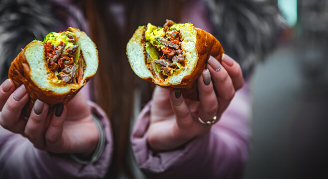 woman hand hold cut Philly cheese steak sandwich with meat, vegetables, cheese and sause
