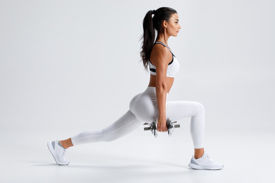 Fitness woman doing lunges exercises for leg muscle training. Active girl doing front forward one leg step lunge exercise