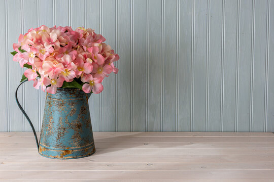 Beautiful pink hydrangea in blue antique watering can.