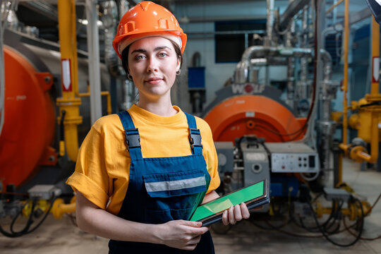 Portrait of a caucasian woman in uniform and helmet with a tablet in her hand. In the background-boiler equipment. Industrial production and boiler house