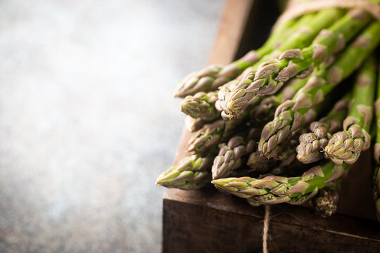 Bunch of fresh green asparagus spears in a box on a rustic background
