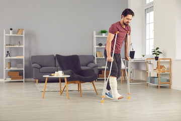 Successful rehabilitation and recovery of people after physical injury such as bone fracture in car or home accident: Young man with broken leg trying to walk with crutches and making good progress