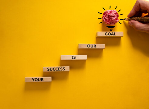 Business concept growth success process. Wood blocks stacking as step stair on yellow background, copy space. Businessman hand. Words 'your success is our goal'. Conceptual image of motivation.