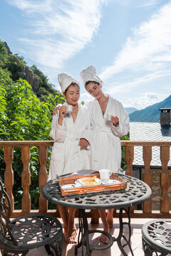 Lovely asian and caucasian lesbian women at a romantic rural getaway weekend. Spa day in shower robe outdoors. LGBT couple enjoying a nice day together