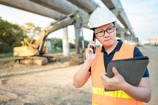 Asian worker man or male civil engineer with protective safety helmet and reflective vest using smartphone and digital tablet for project planning and checking schedule at construction site.