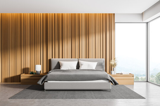 Corner of master bedroom with wooden walls, panoramic window with countryside view, comfortable king size bed standing on gray carpet and concrete floor.