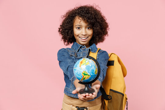 Friendly little african american kid school girl 12-13 years old in casual clothes backpack hold in palm giving Earth world globe isolated on pastel pink background studio Childhood education concept
