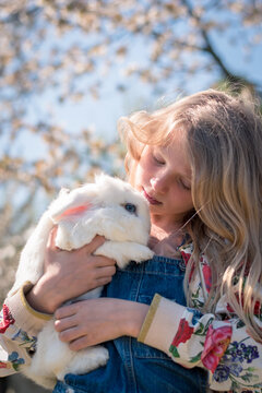 child whispering to white rabbit with blue eyes, friends forever