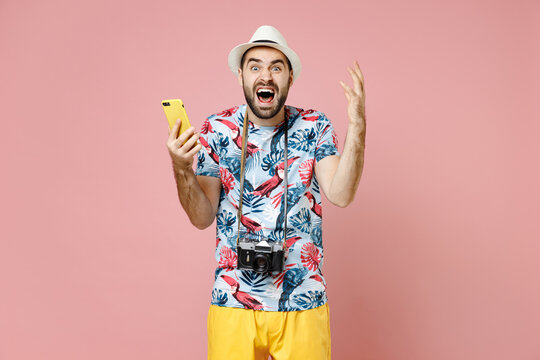 Angry traveler tourist man in summer clothes hat using mobile cell phone typing sms message screaming swearing isolated on pink background. Passenger traveling on weekends. Air flight journey concept.